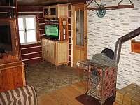 Pohled z obývacího pokoje na kamna a televizi - pronájem roubenky Víchová nad Jizerou