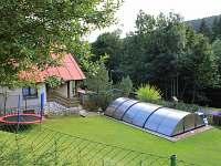 Upravená zahrada s vytápěným bazénem a trampolínou
