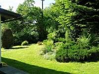 Zahrada před chatou s výhledem na parkoviště