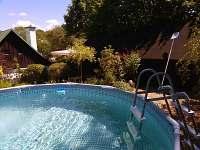pohled přes bazén na zadní část zahrady