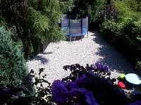 pohled z velké ložnice na spodní část zahrady s trampolínou