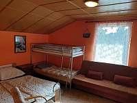 Pokoj ve druhém patře se čtyřmi lůžky, skříní a pohovkou