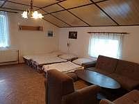 Pokoj ve druhém patře se pěti lůžky, skříní, televizí.
