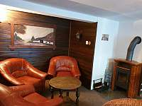 Společenská místnost s posezením, krbovými kamny a televizí.