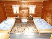 Ložnice v přízemí s lůžky, skříní, nočním stolkem a lampičkou - chalupa k pronajmutí Františkov