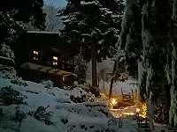 Hájenka v zimě před setměním s rozsvícenými lucerničkami u cesty - chalupa ubytování Krupka