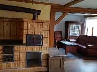 Kachlová kamna s pohledem k obývací části.