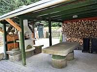 Kryté sezení a grill u kamenneho stolu