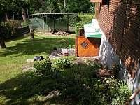 část zahrady se stáním pro auto a vstupem do přízemí - chata ubytování Pyšely