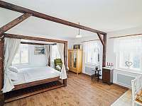 Obývací pokoj a postel s nebesy, kde se u krbu náramně odpočívá - pronájem chalupy Osečnice