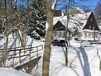 pohled od lyžařského areálu na zasněženou chalupu s lávkou přes potok - Bartošovice v Orlických horách