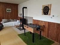 Společenská místnost s krbovými kamny a herním koutkem