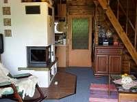 Obytná místnost-krb, houpací křeslo, schodiště - chata k pronájmu Čenkovice