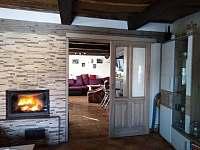 Pohled z obývacího pokoje do krbovny s barem.