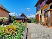Chalupa sa nachádza v zadnej časti záhrady, dom majiteľov je v popredí - chata k pronájmu Lubela - Liptov