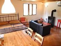 Obývací pokoj s jídelním stolem, manželskou postelí a krbovými kamny.
