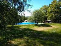 Pohled k osadě přes bazén - chatky k pronájmu Hnačov