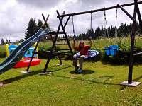 Dětské hřiště s houpačkami a klouzačkou.