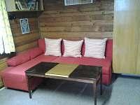 Obývák s rozkládacím gaučem ve druhé chatě.