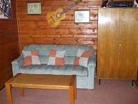 Obývák s TV a rozkládacím gaučem pro 2 osoby.