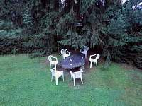 Kamenný stůl v dolní úrovni pozemku pod vzrostlým smrkem