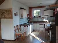 kuchyň propojená s obývákem s krbovými kamny - chata k pronájmu Dolní Jílovice