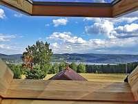 výhled ze střešního okna z pokoje v podkroví na lipenskou přehradu a město vlevo - pronájem chaty Slupečná