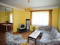 Obývací pokoj - sedací souprava, TV, ve skříňkách prospekty o okolí, hrací stůl