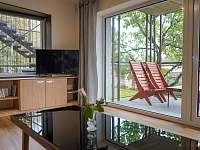 Obývací pokoj s výhledem do zahrady a posezení na terase - apartmán k pronájmu