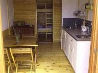 Pohled do hausbótu, kuchyňský kout se stolem a židlemi, vzadu průchod k palandám