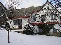 Chalupa a terasa ze zahrady v zimě