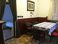 Jídelní stůl v obývací místnosti. Po levé straně je vstup do dolní ložnice. - pronájem chalupy Havlíčkova Borová