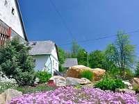 Chalupa za kvetoucím záhonem