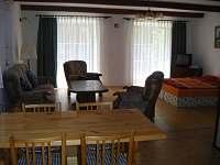 společenská obývací místnost s velkými křídlovými okny vedoucími na zahrádku