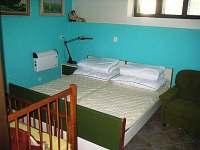 Ložnice pro dvě osoby plus dětská postýlka.