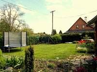 Zahrada a koutek s trampolínou a vzadu houpačky