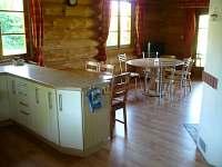 Část kuchyně a jídelní stoly