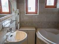 Koupelna s rohovou vanou a WC - společná pro samostatné pokoje