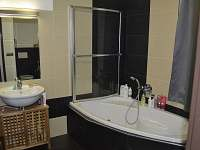 Koupelna s vanou se sprchovým paravanem