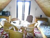 Podkrovní ložnice se sezením a třemi lůžky.